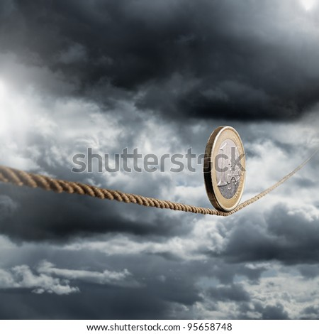 Euro coin balancing on a tightrope. - stock photo