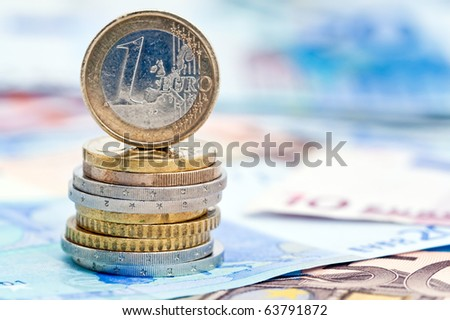 Euro coin balancing on stack with background of banknotes. - stock photo