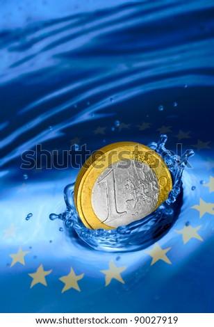 Euro coin falling to the water. European financial crisis metaphor. - stock photo