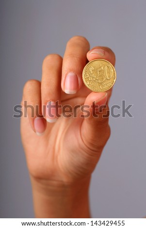 Euro coin in hand over gray background. - stock photo