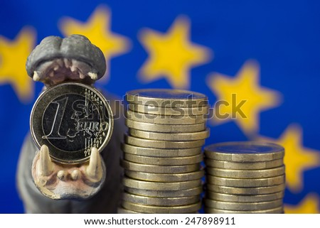 Euro coin in mouth of hippo figurine, EU flag - stock photo