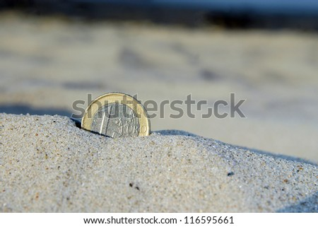 Euro coin in the sand, lost money - stock photo