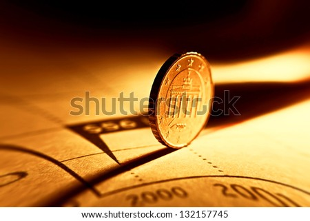 Euro coin on a graph. Financial up and down trend. Pincushion lens use. - stock photo