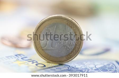 Euro coin on banknotes (detailed macro shot; selective focus) - stock photo