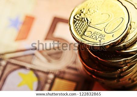 Euro coin on 50 euro banknote. Selective focus. - stock photo