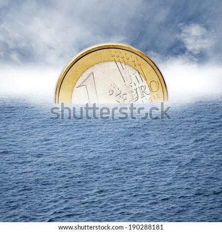 Euro coin sinks into the sea. - stock photo