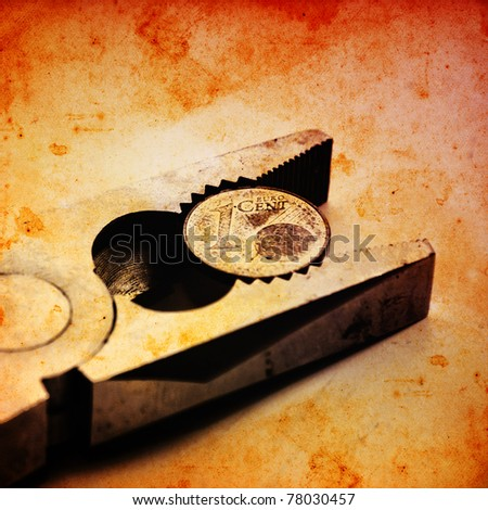 Euro coin squeezed in a clamp. - stock photo