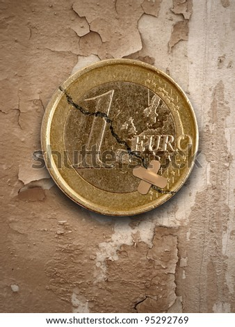 euro coin with crack and sticking plaster - stock photo