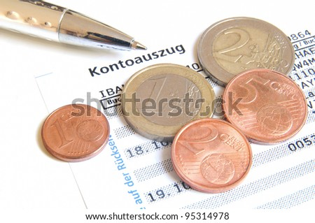 Euro coins and ball pen on top of a bank statement - stock photo