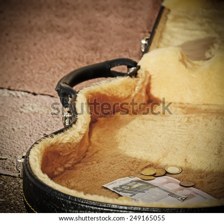 euro coins and bills in a guitar case in vintage tone - stock photo