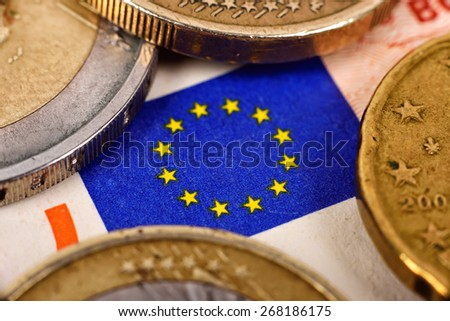 Euro coins and flag on euro banknotes - stock photo
