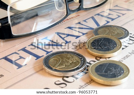 Euro coins , black glasses and the lettering Finances in German language - stock photo