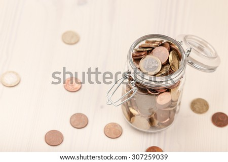Euro coins in the glass jar and on wooden table