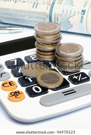 Euro coins on a calculator with ball pen and stock exchange charts in background - stock photo