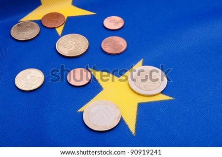 Euro Coins on Blue Flag of European Union - stock photo