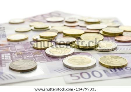Euro coins on 500 Euro banknotes. - stock photo