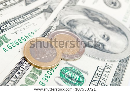 Euro coins on the american Dollar-bills - stock photo