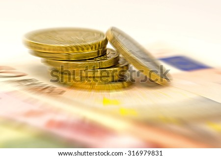 Euro coins resting on banknotes with moton blur