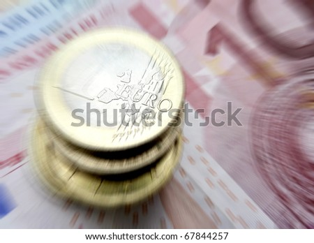 Euro coins resting on banknotes with zoom effect