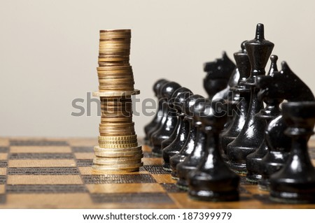 Euro coins stacked like a king on a chess board - stock photo