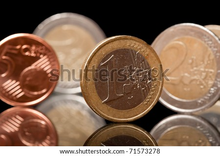 Euro coins with reflection on black isolated background