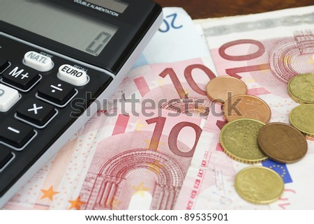 euro converter with euros bills and coins on a wooden table