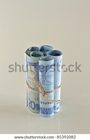 Euro crisis.Euro bills tied with string.  Money is tied up or tight concept. - stock photo