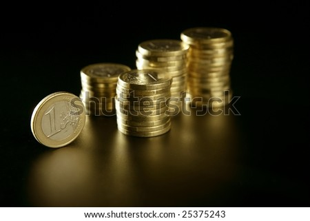 Euro currency coin columns with golden reflections over black