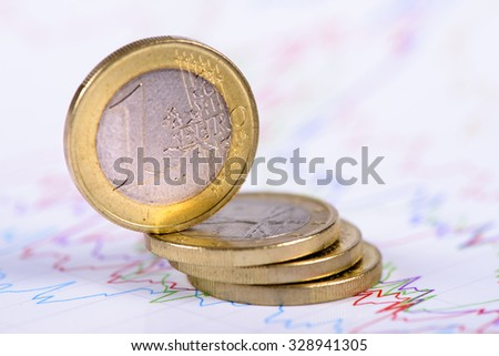 Euro currency with stacked coins as symbol for risk and crisis
