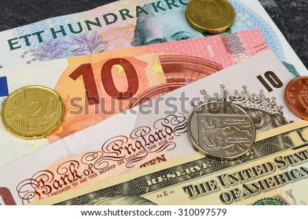 Euro, Dollar, Kroner and Sterling notes on a slate background. - stock photo