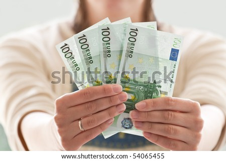 euro in the women's hands. money in focus - stock photo