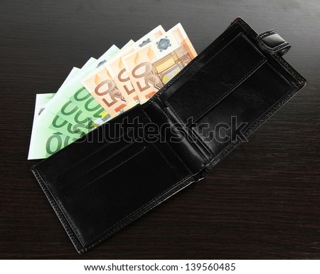 Euro in wallet on wooden background - stock photo