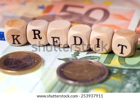 Euro money and wooden cubes with the german word Credit / Credit - stock photo