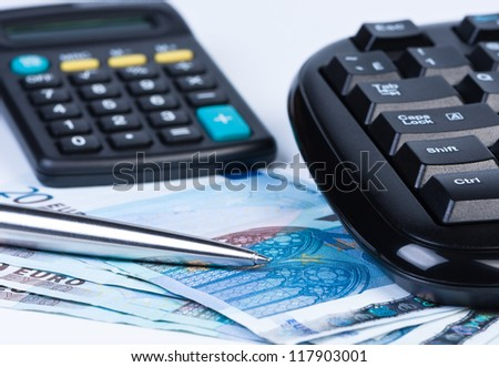 Euro money calculator, keyboard and ball pen close up