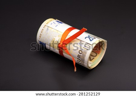 euro money in a red ribbon on black - stock photo