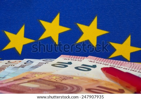 Euro notes and red pencil, EU flag - stock photo