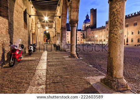 Europe Italy Mantua ancient roman town and Ducale residence at sunset central square covered with cobblestone surrounded by churches, towers, palace, colonnade, cafes all illuminated - stock photo