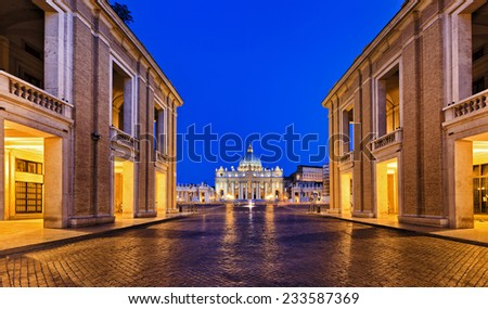 Europe Italy Vatican St Peter Cathedral and square entrance from the street with cobblestone and surrounding Rome buildings illuminated by lights at sunrise - stock photo