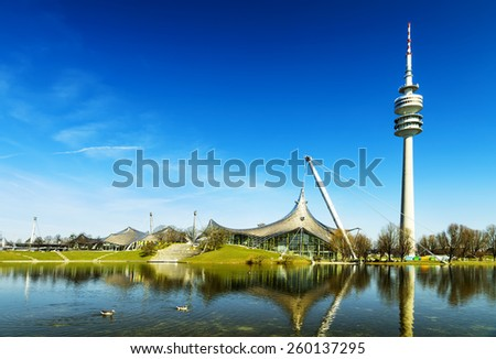 Europe MUNCHEN GERMANY - MARCH 10 2015: Olympiapark Munchen (Olympiahalle) and the lake as seen on MARCH 10 2015. The Park was constructed for the 1972 Summer Olympics which took place in Germany - stock photo