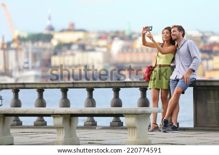 Europe travel. Romantic couple tourists in Stockholm taking selfie photo having fun enjoying skyline view and river by Stockholms City Hall, Sweden. - stock photo