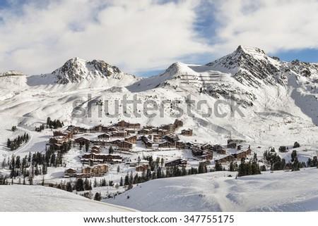 European alpine landscape of brown chalet village ski resort at winter - stock photo