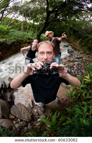 European and American couple near river with nature guide - stock photo