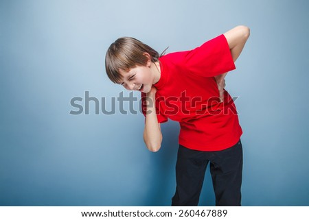 European appearance boy ten years back pain and neck, sciatica on a gray background - stock photo