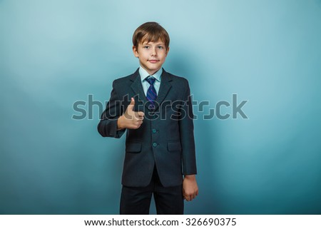 European appearance teenager boy in a business suit shows a sign yes on a gray background, the seriousness of the