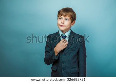 European appearance teenager boy in a business suit straightens tie businessman, confident smile