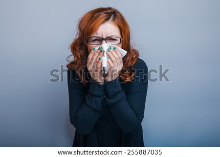 European appearance woman in glasses haired handkerchief on a gray background, disease, rhinitis - stock photo