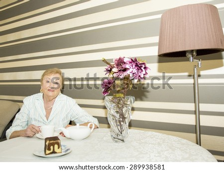 European blond lady in ages drinking tea, teapot, cup, biscuit, bouquet of flowers on table and standard lamp. - stock photo