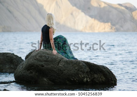 European blonde woman is resting on the seashore. Summer landscape with sea and mountain views. Sunny weather in the morning