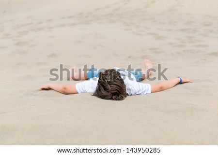 European boy is lying on the white sand in clothes outstretched hands