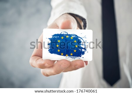 European Businessman holding business card with European union Flag. International cooperation, investments, business opportunities concept. - stock photo